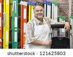 Portrait of happy middle-aged store clerk standing by multicolored ladders in hardware shop - stock photo