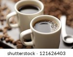 coffee cup filled with coffee beans - stock photo