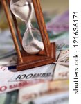 Time is money. A sand-glass and the European currency - stock photo