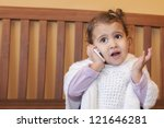 Little girl looking up and speaking by cell phone, - stock photo