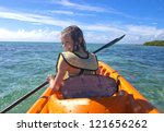young girl kayaking on turquoise waters of the caribbean - stock photo