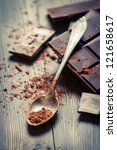 Cocoa Powder and Dark Chocolate on old table - stock photo