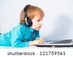 Little kid watching a movie on laptop computer with headphones on his head - stock photo