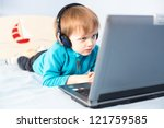 Little boy with headset using laptop - stock photo