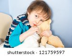 Sick little boy checking his body temperature and holding teddy bear - stock photo