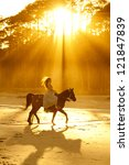 backlit woman in formal dress riding horse on beach - stock photo