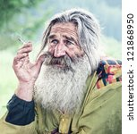portrait of smoking old man with gray beard - stock photo