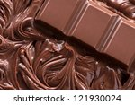 Close up of molten chocolate and piece of chocolate bar - stock photo