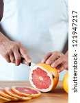 Vertical shot of female hands slicing a fresh grapefruit - stock photo