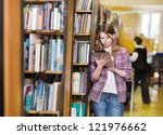 Young focused student using a tablet computer in a library - stock photo
