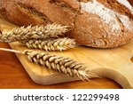 Fresh baked loaf with wheat ears on wooden breadboard - stock photo