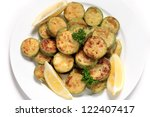 Zucchini or courgette rings dipped in seasoned flour and fried in olive oil, a traditional mediterranean side-dish,plate,lemon,parsley,garnished,cooked, - stock photo