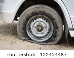 Deflated damaged tyre on white car wheel - stock photo