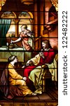 Stained glass window depicting visit of Jesus to home of Martha and Mary, with Mary sitting at feet of Jesus and Martha doing housework - stock photo