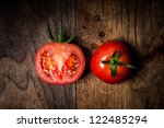 half and whole tomatoes on brown textured wood - stock photo