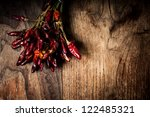 dried hot red chilies on brown textured wood - stock photo