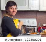 Woman in kitchen cooking a meal on the stove - stock photo