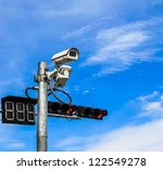 surveillance camera and traffic light against blue sky - stock photo