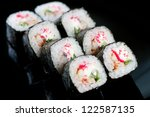 Black plate with a set of Dragon rolls, studio shot - stock photo