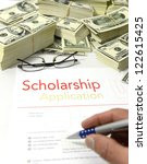 Scholarship application form  with a with a bunch of  US dollar bill - stock photo