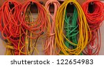 Colorful heavy duty extension cords hanging in carpenter shop - stock photo