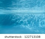Underwater swimming pool ledge with sunlight patterns. - stock photo