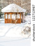 Snow-covered summerhouse in park in winter - stock photo