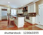 Large white luxury kitchen with cherry hardwood and stone tiles. - stock photo