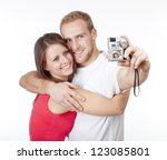 happy young couple taking pictures of themselves - isolated on white - stock photo