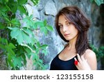 Beautiful brunette next to a wall - stock photo