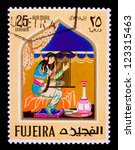 Small photo of FUJAIRAH - CIRCA 1967: A stamp printed in Fujairah shows the image of a playing woman from the story of Ali Baba, circa 1967.