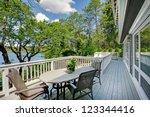 Large long balcony home exterior with table and chairs, lake view. - stock photo