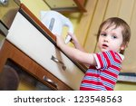 Little boy is reaching eletrical kettle with hot water - stock photo