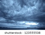 The dark clouds on the coastline - stock photo