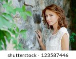 Portrait of a innocent looking brunette next to a stone wall - stock photo