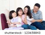 asian family sitting on sofa | Shutterstock . vector #123658843
