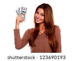 Small photo of Portrait of a charming and smiling young woman with cash money against white background