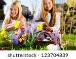 Children on an Easter Egg hunt on a meadow in spring, a living Easter Bunny is sitting in the Easter basket - stock photo