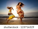 Mother and daughter jumping and dancing on beautiful beach. - stock photo