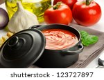Tomato soup in a black casserole and ingredients - stock photo