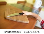 Little baby boy is reaching kitchen knife - danger in kitchen - stock photo