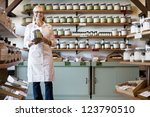 Portrait of a happy senior merchant standing with spice jar in store - stock photo