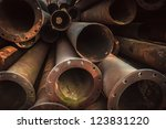 Rusty old pipes stacked up with natural light on them - stock photo