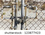 Rusted gate is lock with a chain. - stock photo