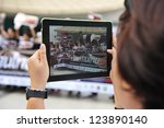 BANGKOK - DEC 9: An passer-by uses an iPad tablet to photograph protesters on Thai Anti-Corruption Day organised by the United Nations Development Programme on Dec 9, 2012 in Bangkok, Thailand. - stock photo