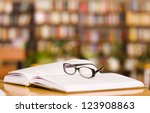book and glasses on table in library - stock photo