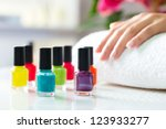 Woman in a nail salon receiving a manicure, there are colorful nail polish - stock photo