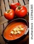 Tomato soup in a earthenware bowl with tomatoes - stock photo