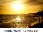Coconut palms and sand beach, people swimming on sunset. - stock photo