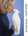 blonde woman showing affection to his white cockatoo - stock photo